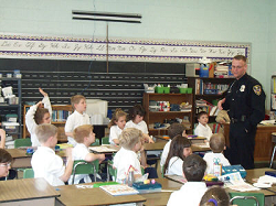 School Resource Officer answering questions for a class of young children